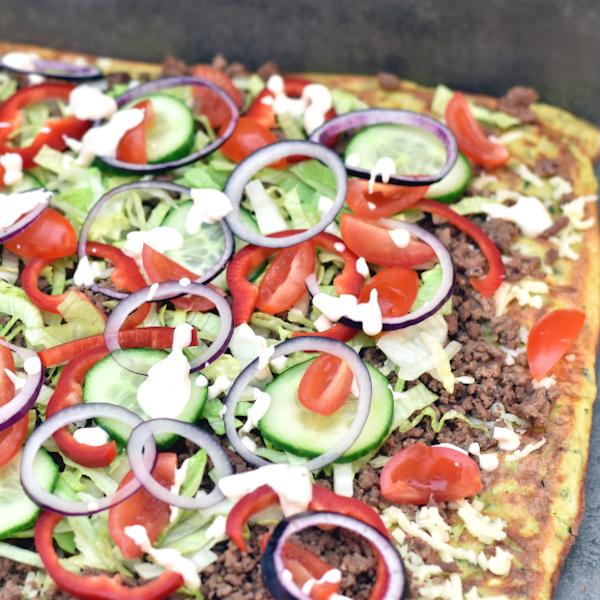Bag en squashbund og kom stegt, hakket oksekød sammen med ost, salat, agurker og tomater ovenpå inden du ruller den sammen og skærer i skiver.